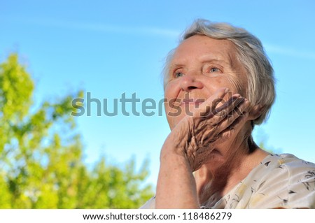 Senior woman looking on sky and smiling. - stock photo