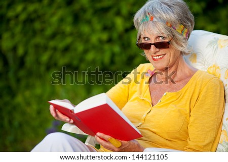 senior woman looking over sunglasses while reading a book - stock photo