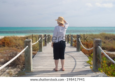 senior woman looks out on the turquoise sea from a boardwalk to the beach - stock photo