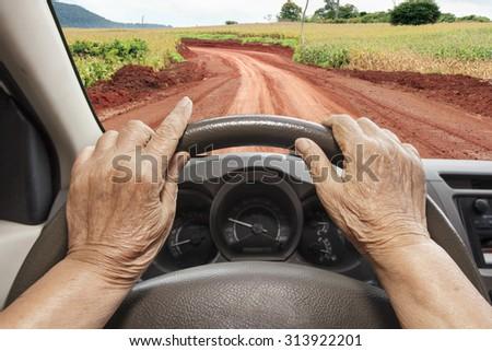 Senior woman lost way on rural road - stock photo