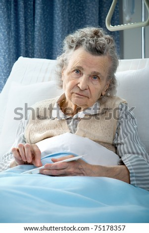 senior woman lying at hospital bed and takes the medicine - stock photo