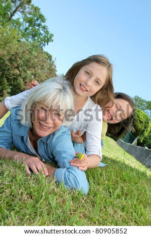 Senior woman lying down in park with girls on his back - stock photo