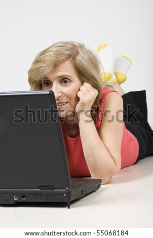Senior woman lying down on floor and looking laptop