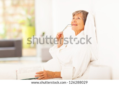 senior woman lying on bed daydreaming - stock photo