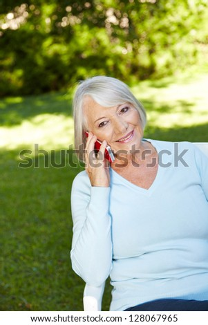Senior woman making a phone call with her smartphone in a garden - stock photo