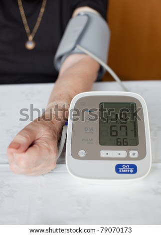 Senior woman measuring her blood pressure. At home. - stock photo