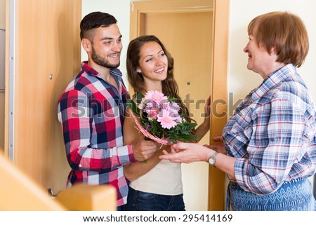 Senior woman meeting  smiling young couple with flowers at the door - stock photo