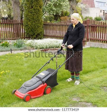 senior woman mowing grass with electric mower in his flower garden