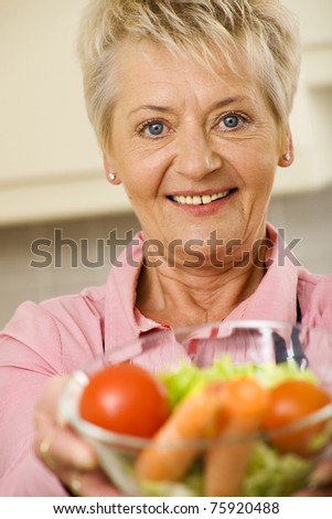 Senior woman offering healthy food in a glass bowl - stock photo