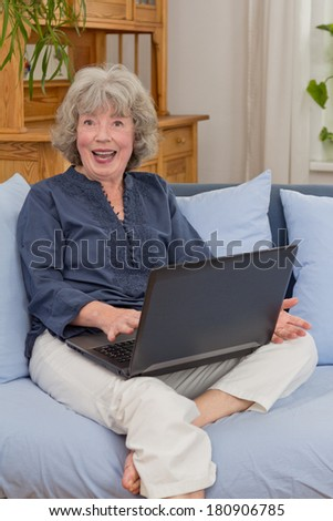 Senior woman on a couch cheering in front of her notebook