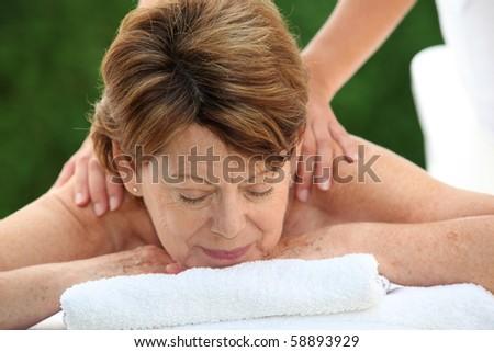 Senior woman on a massage bed - stock photo