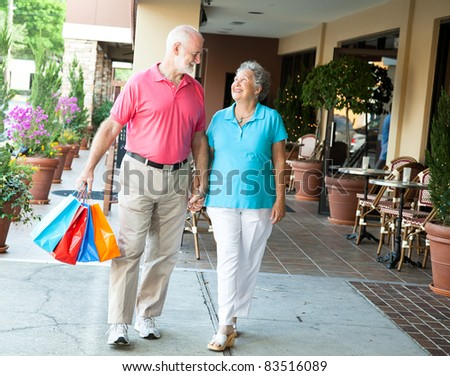 Senior woman on a shopping spree looks up at her handsome husband who's carrying her bags. - stock photo
