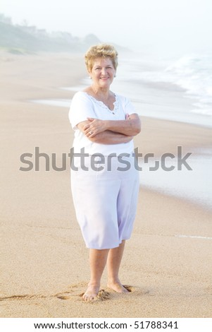 senior woman on beach at sunset - stock photo