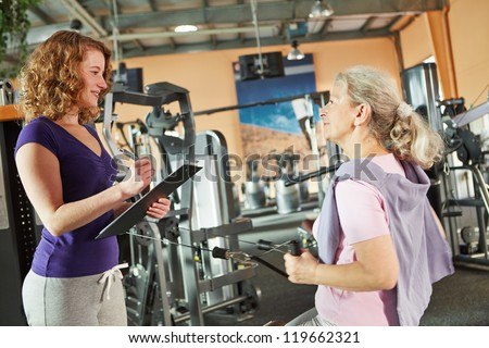 Senior woman on cable machine in fitness center listening to fitness instructor - stock photo
