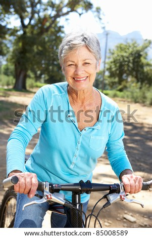 Senior woman on country bike ride - stock photo