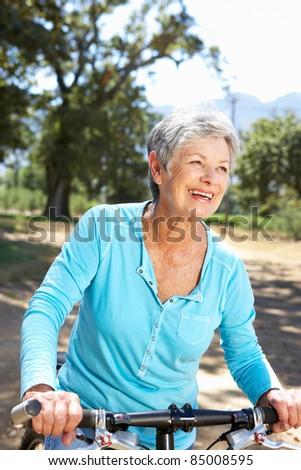 Senior woman on country bike ride - stock photo