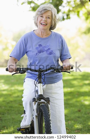 Senior woman on cycle ride in countryside - stock photo