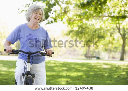 Senior woman on cycle ride in park - stock photo