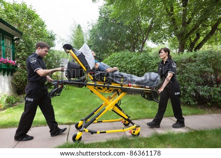 Senior woman on emergency medical stretcher being transported from home - stock photo