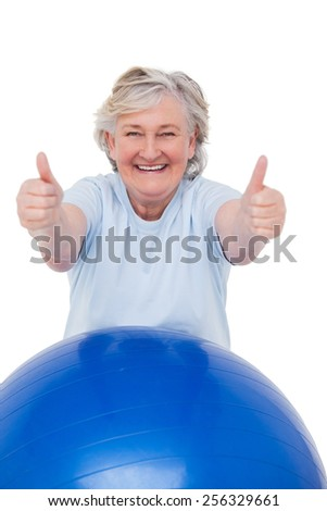 Senior woman on exercise ball with thumbs up on white background - stock photo