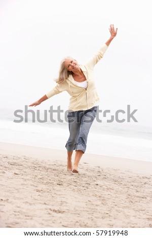 Senior Woman On Holiday Running Along Winter Beach - stock photo
