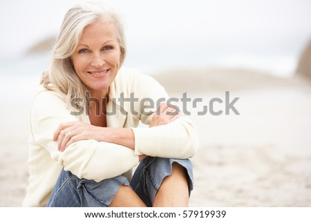 Senior Woman On Holiday Sitting On Winter Beach - stock photo