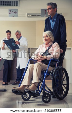 Senior woman on the wheelchair with her caregiver. Hospital background.