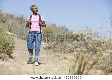 Senior woman on walk in countryside - stock photo