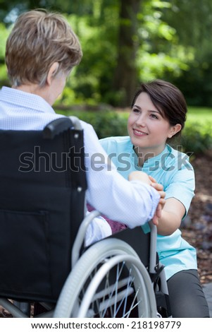 Senior woman on wheelchair with her caregiver outside - stock photo