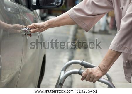 senior woman open car door with walker on street. - stock photo