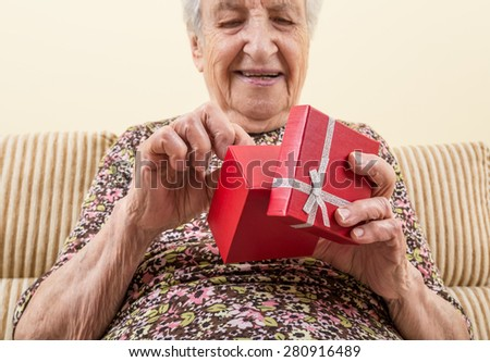 senior woman opening gift - stock photo