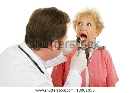 Senior woman opening her mouth for the doctor to look inside.  Isolated on white background.