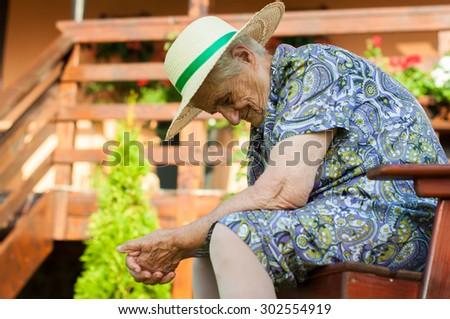 Senior woman outdoors relaxing in summer - stock photo