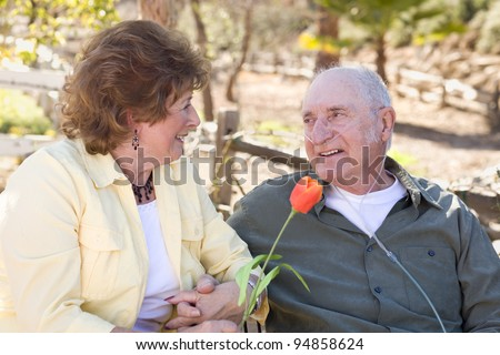 Senior Woman Outside with Seated Man Wearing Oxygen Tubes. - stock photo