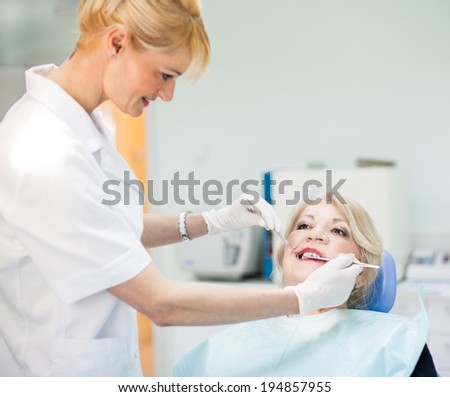 Senior woman patient and her dentist smiling