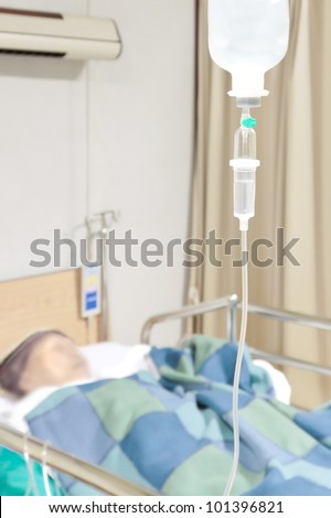 Senior woman patient in the hospital bed saline intravenous (iv) drip - stock photo