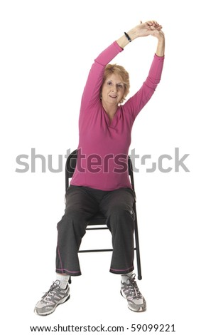 Senior woman performing arm stretch on chair. White background - stock photo