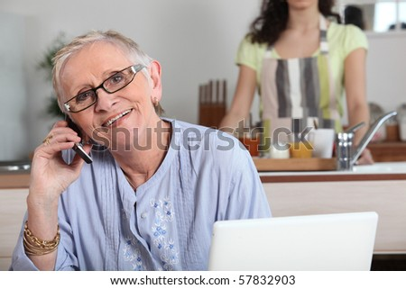 Senior woman phoning in front of a laptop computer - stock photo