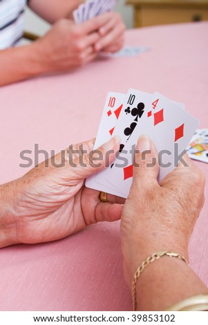 senior woman playing cards - stock photo