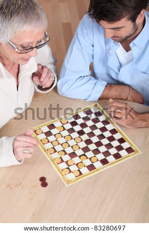 Senior woman playing checkers with a young man - stock photo