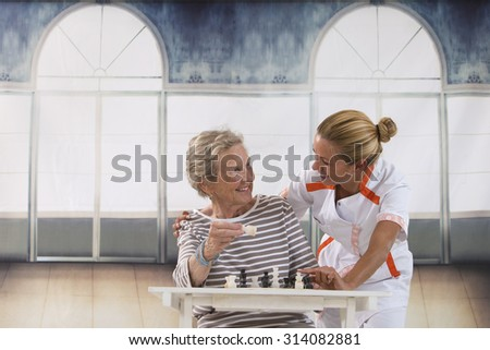 Senior woman playing chess with a nurse in a retirement home - stock photo