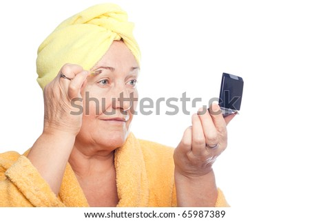 Senior woman pluck eyebrows - stock photo