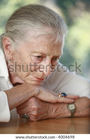 Senior woman pondering. Shallow DOF. - stock photo