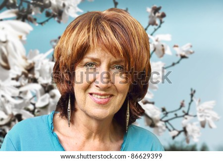 Senior woman portrait in front of white blooming  tulip tree - stock photo