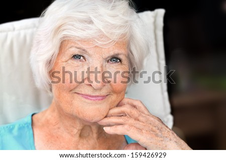 Senior woman portrait, looking relaxed with hand on chin - stock photo