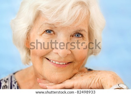 Senior woman portrait, on blue background with white hair - stock photo