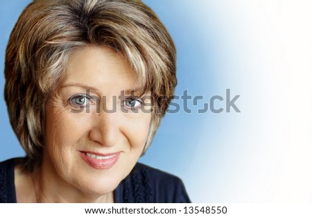 Senior woman portrait on blue white background - stock photo