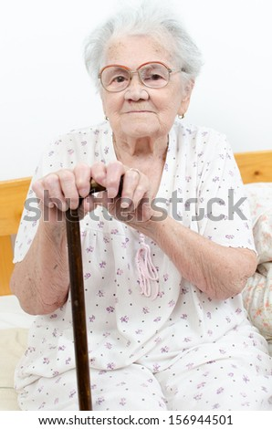 Senior woman portrait, on grey background with walking stick