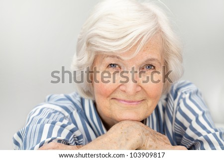 Senior woman portrait, on  grey  background with white hair