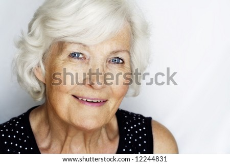 Senior woman portrait on grey with copy-space - stock photo